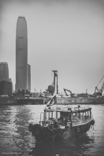 A small junk docked in the bay with Kowloon's towers in the background.