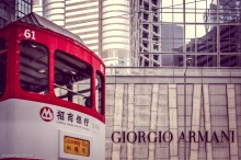 A street tram passes in front of luxury shops clustered around Central neighborhood.