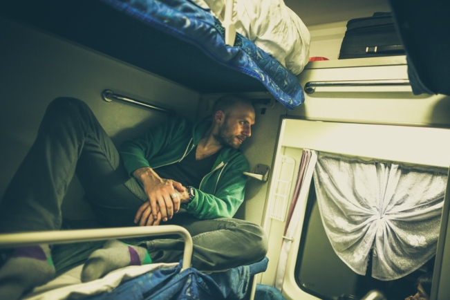 Seb peers into the train corridor from his sleeper berth