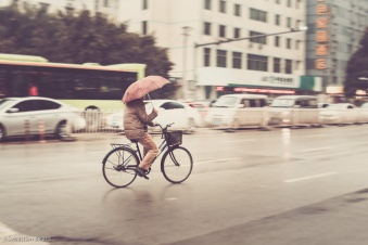 A bicyclist stays dry on a misty morning in Nanning, China. February 2014.
