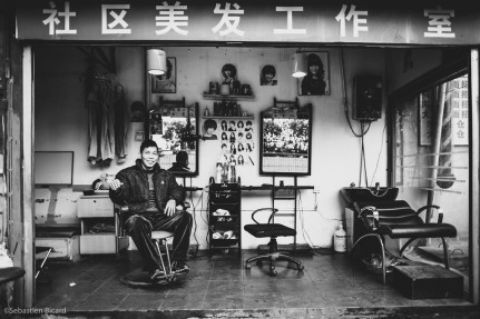A barber in his shop near the train station. Haircut and wash for around $1. Nanning, China, February 2014.