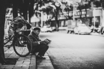 An elderly man takes a break from riding his bike to read the news. Nanning, China, February 2014.