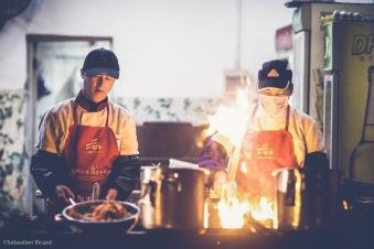 Cooks serve up stir-fried noodles in a street food restaurant. Nanning, China, February 2014.