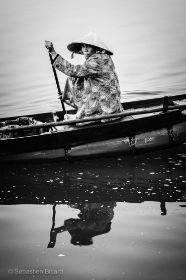 A woman paddles her canoe across the narrow river near Hoi An. Vietnam, March 2014.