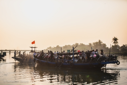 Early morning commuters with their motorbikes take the river ferry to Hoi An. Vietnam, February 2014.
