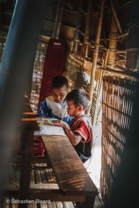 Two schoolboys study before class in a bamboo school room of a village outside of Kon Tum, Vietnam.