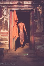 A Buddhist monk heads for the showers while his freshly laundered robes dry in the sun. Phnom Penh, Cambodia, March 2014.