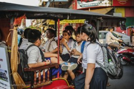 School children crowd into a tuk-tuk for a ride home in the late afternoon. Phnom Penh, Cambodia, March 2014.
