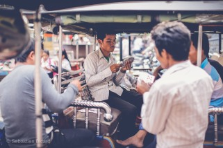 Tuk-tuk drivers deal up a hand of cards in the hope of earning a couple riels between customers. Phnom Penh, Cambodia, March 2014.