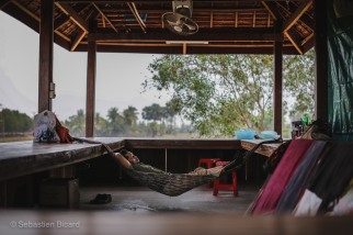 A man takes full advantage of the rest stop on the road from Phnom Penh. Cambodia, March 2014.