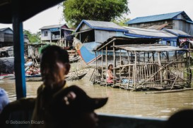 Local passengers keep cool in the shade of the slow boat as we put past floating villages on the way to Siem Reap. Cambodia, March 2014.
