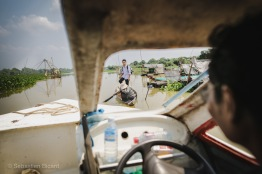 A passenger gets ferried from a small village to the waiting slow boat. Cambodia, March 2014.