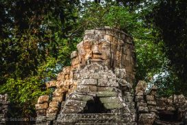 The sun rises on a stone face guarding one of the entrances to Banteay Kdei temple. Angkor, Cambodia, March 2014.