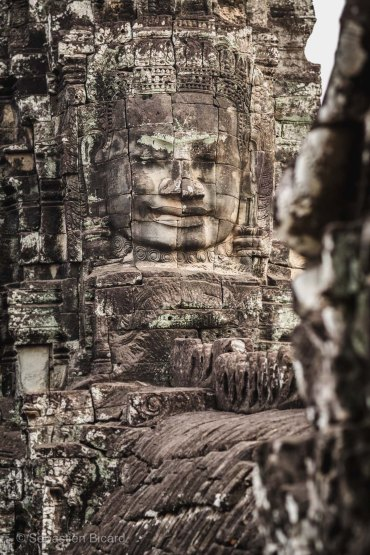 One of the 216 stone faces carefully carved into the façades of Bayon. Angkor, Cambodia, March 2014.