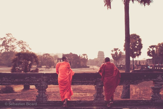 Monks pause to enjoy the view of Angkor Wat at sunset.