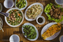 An afternoon feast of vegetables, fruit, noodles, meat and fish prepared by a local family in Mai Chau. Vietnam, February 2014.