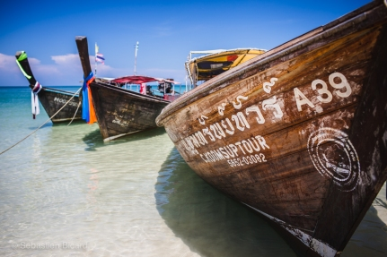 Longboat taxis await passengers on dramatic and colorful Railay Beach. Thailand, May 2014.