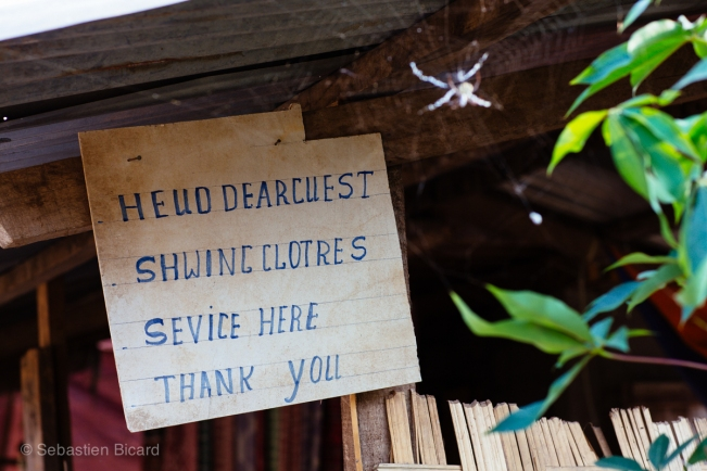 "Even in the remote and difficult to access village of Mong Ngoi, English signs attest to the ever present flow of backpackers and their needs. This sign reads  (in Lao-tinted English) ""Hello Dear Guest. Sewing clothes service available here."""
