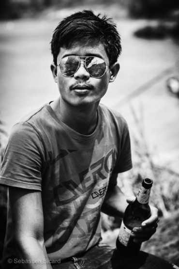 A young man enjoys a beer with his friends during the river boat races. Nong Khiaw, Laos, April 2014.