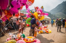 A balloon vendor prepares for a day at the annual river boat races. Nong Khiaw, Laos, April 2014.