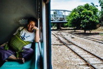 A local man has grabbed a relatively comfortable seat near the wall on Yangon's Circular Train. Myanmar, May 2014.