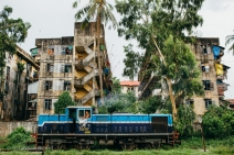 A locomotive near some of Yangon's suburban apartment buildings. Myanmar, May 2014.