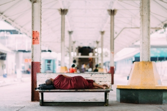 A monk takes a nap in the Yangon central rail station. Myanmar, May 2014.