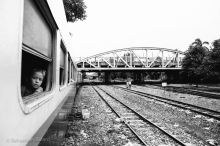 A child peers out the window of the passenger train. Myanmar, May 2014.
