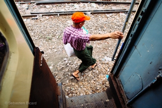 A man disembarks from the still moving train. Myanmar, May 2014.