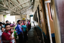 Passengers wait to board the train in a small country station. Myanmar, May 2014.