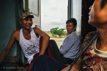 Passengers find an open place to sit in the space between coaches. Myanmar, May 2014.