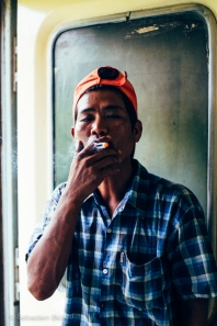 A passenger smokes a cheroot cigarette in the Ordinary Class train from Yangon to Pyay, Myanmar. May 2014.