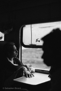 A teenage girl peers out the open train windows on the way to Pyay, Myanmar. May 2014.