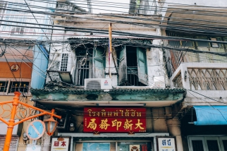 City electric cables hang in front of a storefront in Chinatown. Bangkok, Thailand, April 2014.
