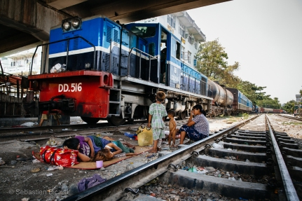 A family avoids the hot midday sun under a train trestle in Mandalay, Myanmar. May 2014.