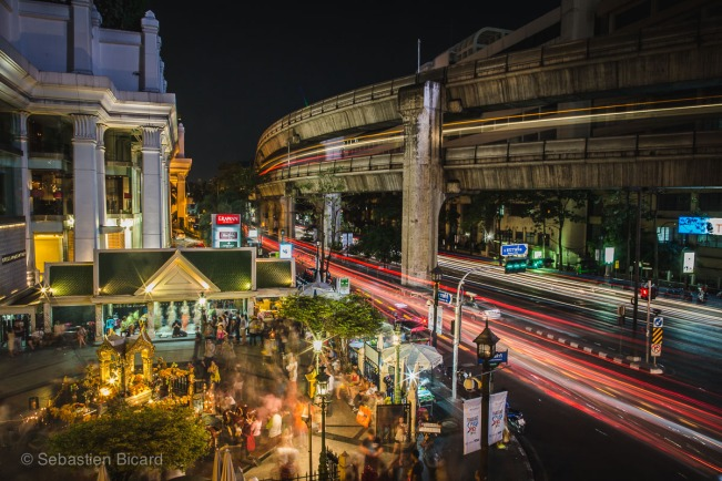 Erawan shrine shines golden in front of the speeding traffic and skywalk.