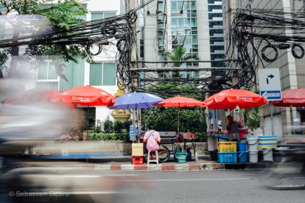 Street food vendors sell cheap and tasty treats along busy avenues Bangkok. Thailand, April 2014.