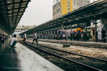 Passengers and workers freely cross the tracks in Hua Lumphong train station. Bangkok, Thailand, April 2014.