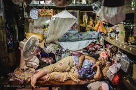 A woman takes a snooze in her crowded shop space in old town Bangkok. Thailand, April 2014.