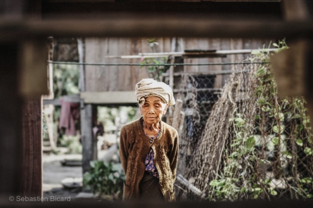 A elderly woman takes a walk around her village in Tad Lo, Laos, March 2014.