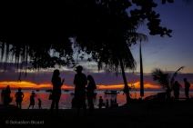 Tourists and dive students take a break from the busy scuba centers on Koh Tao to enjoy a dramatic island sunset. Thailand, May 2014.