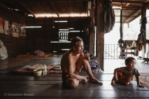 Grandfather and his grandson get comfortable on the wooden floor of the traditional stilt house. Ban Phon Kham, Laos, April 2014.