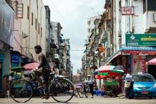 A man rides a bike through downtown Yangon. Myanmar, May 2014.