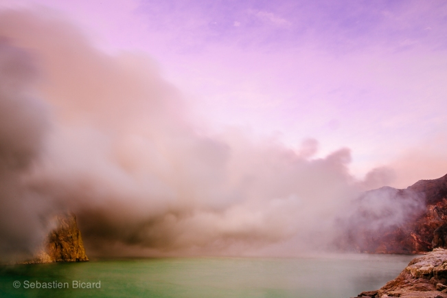 The pink sunrise contrasts with the yellow fumes and turquoise acid in the crater of Kawa Ijen.