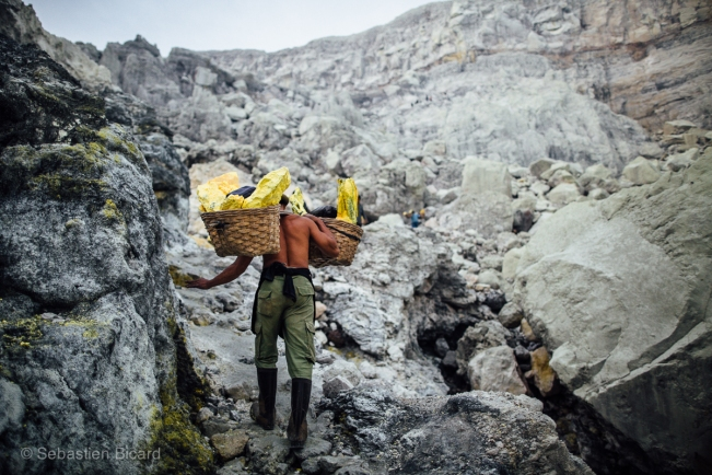 Like something from a science fiction movie, the toxic yellow stones get carried out of the gray moonscape crater.