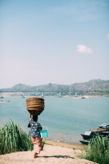 A woman carries baskets towards the Irrawaddy River in Pyay. Myanmar, May 2014.