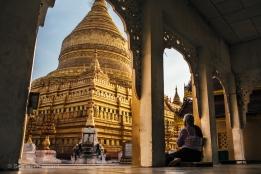 An elderly woman prays near Shwezigon pagoda in Bagan. Myanmar, May 2014.