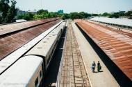 Travelers arriving via train walk along the platform in Mandalay. Myanmar, May 2014.