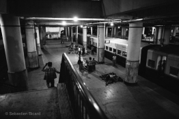 Weary travelers sleep on the platform before departing from the Mandalay train station at 4am. Myanmar, May 2014.