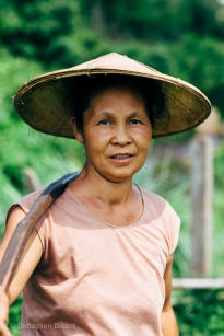 A village woman carries drinking water back to her home outside Hsipaw, Myanmar, May 2014.